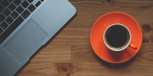 Oranssi kahvikuppi ja laptop pöydällä