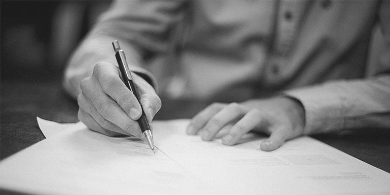 Henkilö allekirjoittaa pöydällä olevaa hankintasopimusta