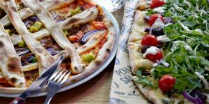 Kaksi Kotipizzan pizzaa vierekkäin pöydällä