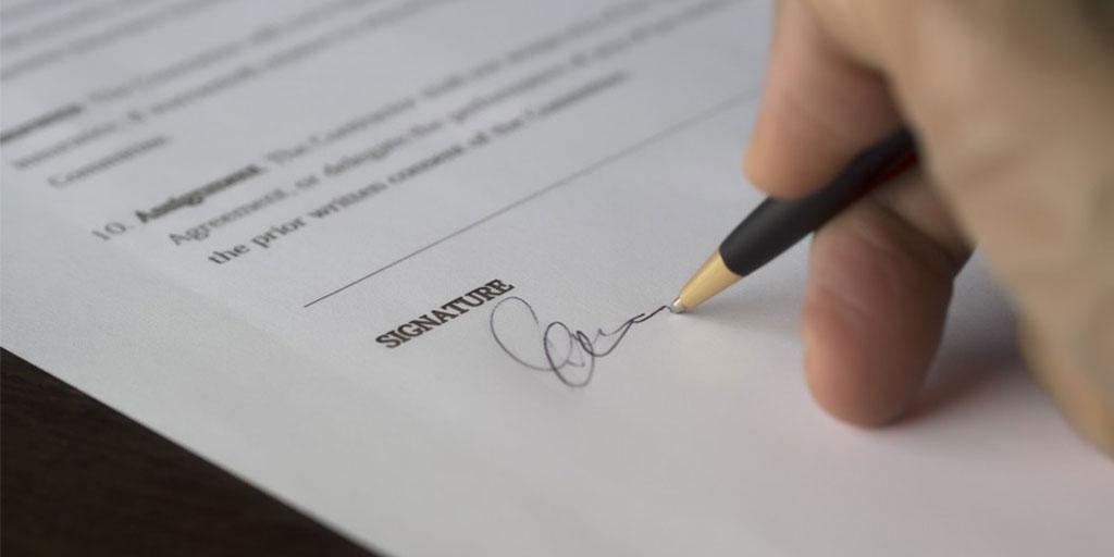 Käsi allekirjoittaa hankintasopimusta